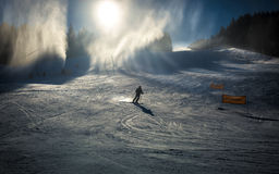 Skier going down the slope under working snow cannons Stock Image