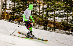 Skier in a Green Morphsuit. Young boy, wearing a green morphsuit and shorts, races down a ski trail Stock Photo