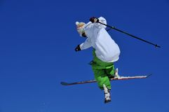 Skier in green and white performing a jump. Skier in green and white performing a tele-heli with crossed skis. Below a trail of snow from the take-off Royalty Free Stock Photos