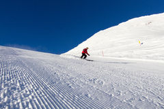 Skier on groomed ski slope Royalty Free Stock Images