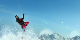 Skier in helmet and glasses makes a jump. Sportsman in action. Winter active sport, extreme lifestyle. Skiing in mountains, blue sky on background Royalty Free Stock Photography