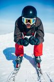 Skier racing from the mountain, front view. Skier in helmet and glasses racing from the mountain, front view. Winter active sport, extreme lifestyle. Downhill Royalty Free Stock Image