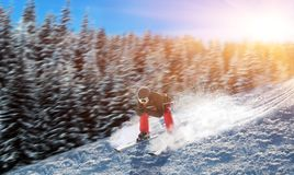 Skier in helmet and glasses racing from mountain. Skier in helmet and glasses racing from the mountain. Winter active sport, extreme lifestyle. Downhill skiing Stock Photos