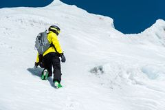 A skier in a helmet and mask with a backpack rises on a slope against the background of snow and a glacier. Backcountry. Freeride royalty free stock images