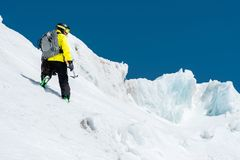 A skier in a helmet and mask with a backpack rises on a slope against the background of snow and a glacier whith ice axe. In your hand. Backcountry Freeride stock photo