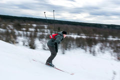 Skier hiker goes downhill in forest virgin snow. Motion blurred image. Royalty Free Stock Images