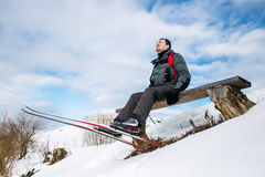 Skier hiker have a rest on bench during winter forest hiking Stock Image