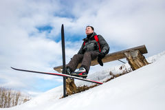 Skier hiker relaxing on bench during winter forest skiing Royalty Free Stock Images