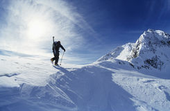 Skier Hiking To Mountain Summit. Rear view of skier hiking to mountain summit Royalty Free Stock Images