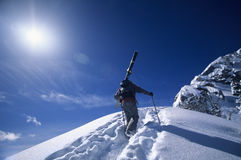 Skier Hiking To Mountain Summit. Rear view of skier hiking to mountain summit against sky Stock Photos