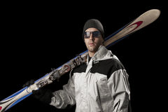 Skier holding a pair of skis Royalty Free Stock Images