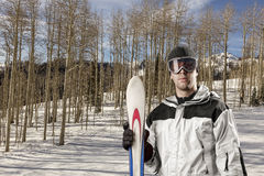 Skier holding a pair of skis Royalty Free Stock Image