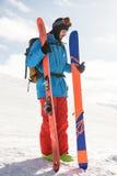 Skier holding ski on the snowy mountains Royalty Free Stock Photos