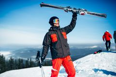 Skier holds skis and poles in hands. Skier in helmet and glasses holds skis and poles in hands, blue sky and snowy mountains on background. Winter active sport Stock Photos