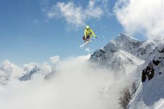 Skier jump in the mountains. Extreme ski sport. Freeride. Skier jump in the snowy mountains. Extreme ski sport. Freeride Stock Photos