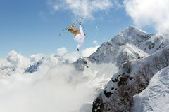 Skier jump in the mountains. Extreme ski sport. Freeride. Skier jump in the snowy mountains. Extreme ski sport. Freeride Stock Photo