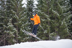 Skier at jump from the slope of mountains. Flying skier man at jump from the slope of mountains in orange jacket looking apprehensive about the landing with Stock Images