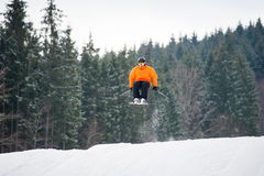 Skier at jump from the slope of mountains. Flying skier at jump from the slope of mountains in orange jacket performing a high jump, with forest in background Stock Photo