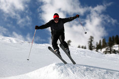 Skier jumping. Skier on a slope against the cloudy sky Royalty Free Stock Image