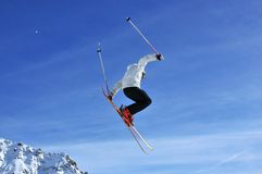 Skier jumping. A skier performing a dramatic jump against a backdrop of mountains and snow Royalty Free Stock Photo
