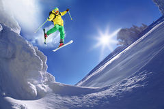 Skier jumping against blue sky from the rock. In high mountain Royalty Free Stock Image