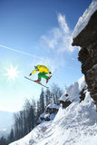Skier jumping against blue sky from the rock Stock Image