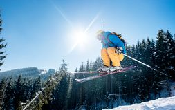 Skier skiing in the mountains. Skier jumping in the air while skiing in the mountains blue sky on the background copyspace sunlight extreme freeride adrenaline stock photo