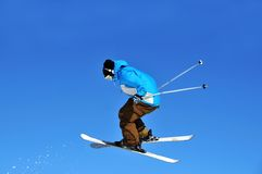 Skier jumping backwards. A skier performing a jump and pointing backwards as evidenced by the snow trailing behind him stock images