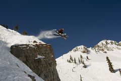 Skier jumping cross tips off cliff Royalty Free Stock Images