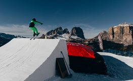 Skier jumping on kicker, balloon landing, Val di Fassa Dolomiti snow park. Mountains on background Royalty Free Stock Photos