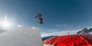 Skier jumping on kicker, balloon landing, Val di Fassa Dolomiti snow park. Mountains on background Stock Images