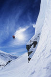 Skier Jumping From Mountain Ledge Stock Photo