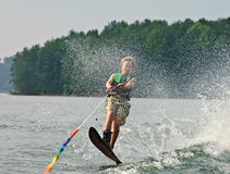 Skier Jumping Over Wake. A young boy on a slalom ski passing over the wake behind the boat with water spray flying in front of him stock photos