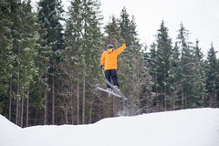 Skier is jumping from the slope of mountains. Flying skier male at jump from the slope of mountains in orange jacket performing a high jump and looking Stock Photography