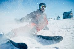 Skier lies on snowy surface of speed slope. Skier in helmet and glasses lies on snowy surface of speed slope, front view. Winter active sport, extreme lifestyle Royalty Free Stock Photography
