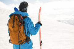 Skier looking at beautiful snow-covered mountains. Rear view of skier looking at beautiful snow-covered mountains Stock Images