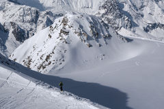 Skier looking down on single ski track before heading down Royalty Free Stock Images