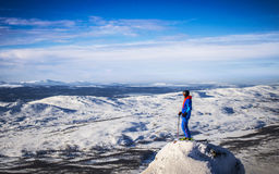 Skier is looking out to the horizon. Skier in blue and orange is standing on a snowtop, looking out towards the horizon with blue mountains Stock Photography