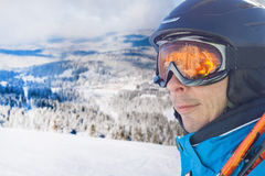 Skier man in the blue skiing jacket, helmet and glasses against snow forest panorama Royalty Free Stock Photography