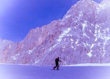 Skier man climbing mountain slope Royalty Free Stock Photos