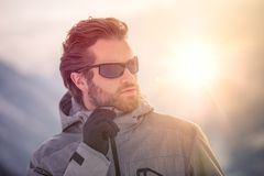 Skier man detail wearing anorak jacket with sunglasses portrait. exploring snowy land walking and skiing with alpine ski. Europe Alps. Winter sunny day, snow royalty free stock photos