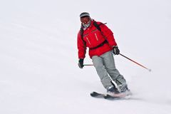 Skier man running down from snowy winter resort mo. Skier man running down from snowy European resort mountain Royalty Free Stock Photo
