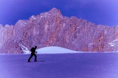 Skier man silhouette climbing mountain Royalty Free Stock Photos