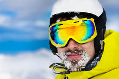 Skier man with snow on beard wear helmet and mask Royalty Free Stock Images