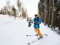 Skier man taking selfie with stick. Focus on his camera Stock Images