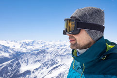Skier man thinking. Portrait of man wearing ski glasses and cap while looking the snowy mountains. Closeup face of sporty guy contemplate the snowy. Satisfied Stock Image