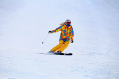 Skier in mask slides fast while skiing from slope Stock Photos