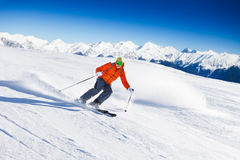 Skier in mask slides fast while skiing from slope Royalty Free Stock Photo