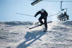 Skier in the moment of falling on the snowy slope Royalty Free Stock Photos