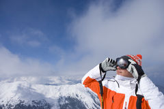 Skier on mountain top adjusting goggles Royalty Free Stock Photo